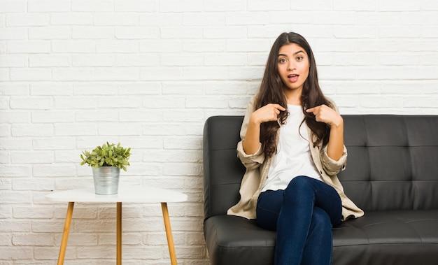 Joven mujer árabe sentada en el sofá sorprendido señalando con el dedo