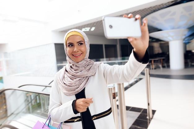 Joven mujer árabe tomando selfie en el moderno centro comercial.