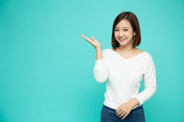Joven mujer asiática elegante sonriendo y presentando al espacio vacío copia aislado sobre fondo verde, modelo tailandés