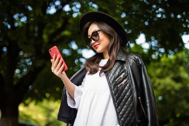 Joven mujer asiática enviando mensajes de texto celular en la calle de la ciudad