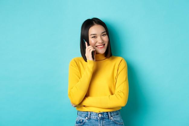 Joven mujer asiática con estilo hablando por teléfono, llamando a un amigo y sonriendo, de pie con el teléfono inteligente sobre fondo azul.