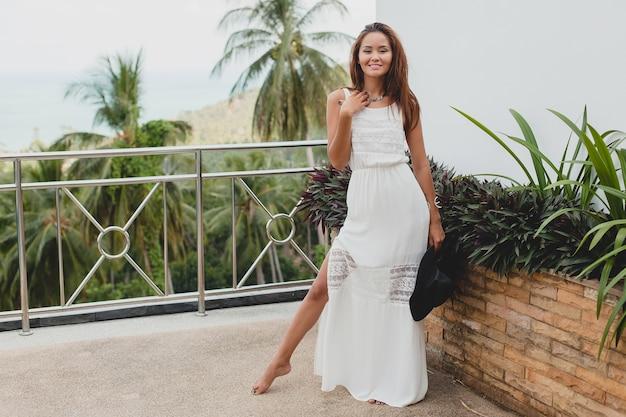 Joven mujer asiática con estilo en vestido blanco boho, estilo vintage, natural, sonriente, feliz, vacaciones tropicales, hotel, fondo de palmeras