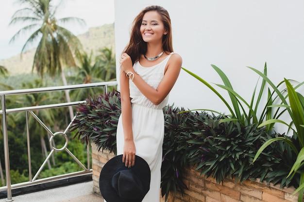 Joven mujer asiática con estilo en vestido blanco boho, estilo vintage, natural, sonriente, feliz, vacaciones tropicales, hotel, luna de miel
