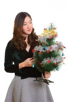 Joven mujer asiática feliz celebración feliz árbol de navidad aislado contra un blanco