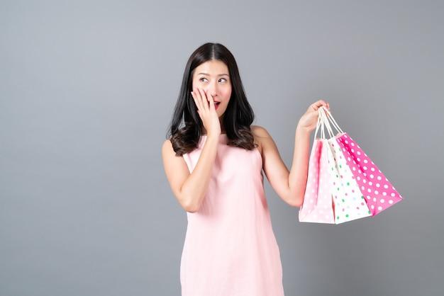 Joven mujer asiática feliz sonriendo con bolsa de compras en vestido rosa