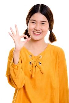 Joven mujer asiática feliz sonriendo mientras da el signo de ok