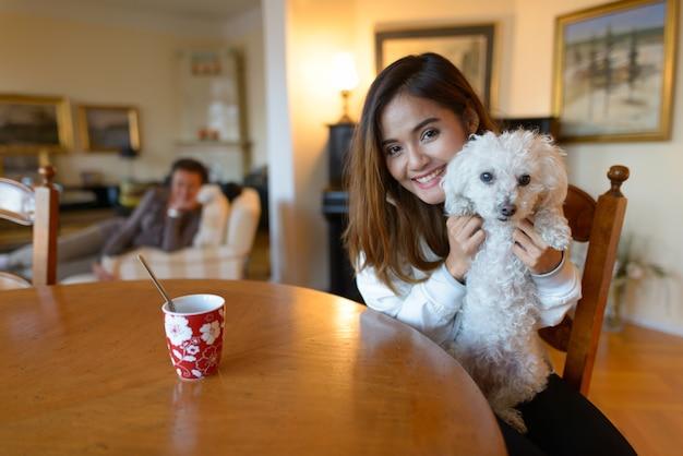 Joven mujer asiática feliz sonriendo mientras sostiene lindo perro dentro de casa cómoda