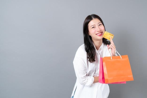Joven mujer asiática feliz sonriendo sosteniendo tarjetas de crédito y bolsas de compras en camisa blanca sobre pared gris