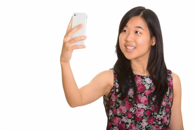 Joven mujer asiática feliz tomando selfie con teléfono móvil aislado