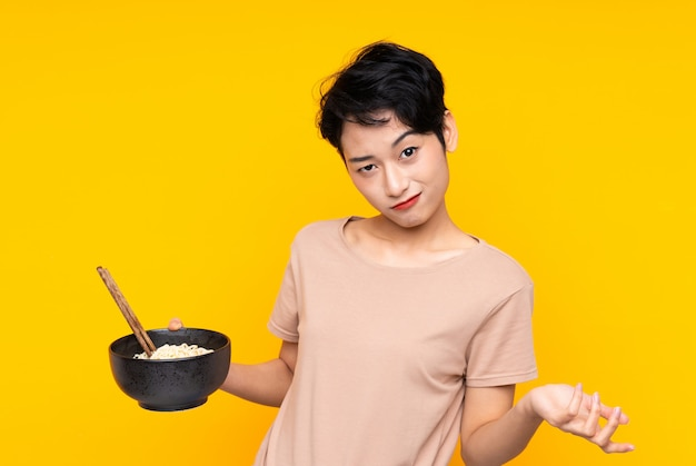 Joven mujer asiática haciendo dudas gesto mientras levanta los hombros mientras sostiene un tazón de fideos con palillos