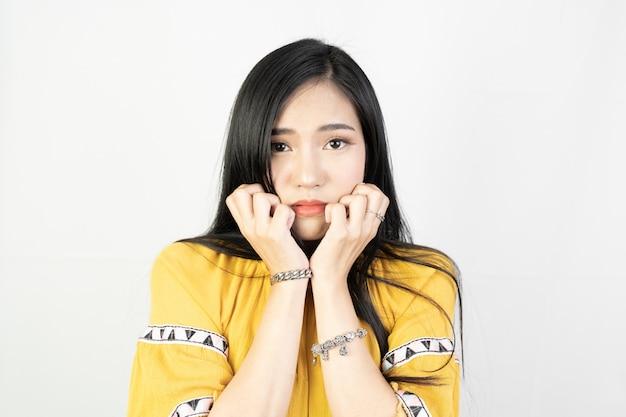 Joven mujer asiática haciendo una expresión tímida en blanco