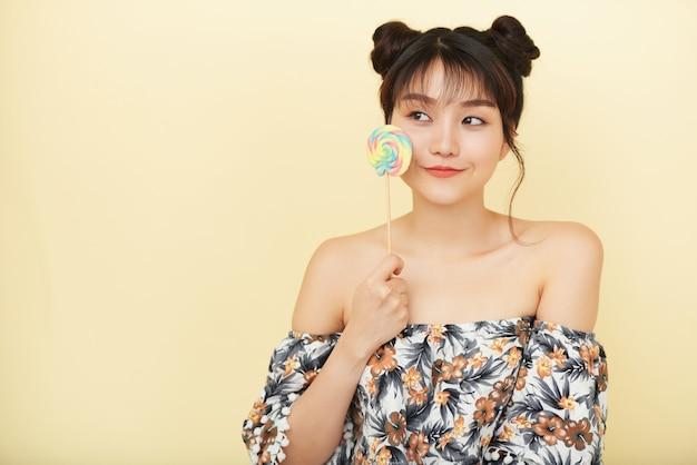 Joven mujer asiática con hombros desnudos posando en estudio y sosteniendo piruleta en la mejilla