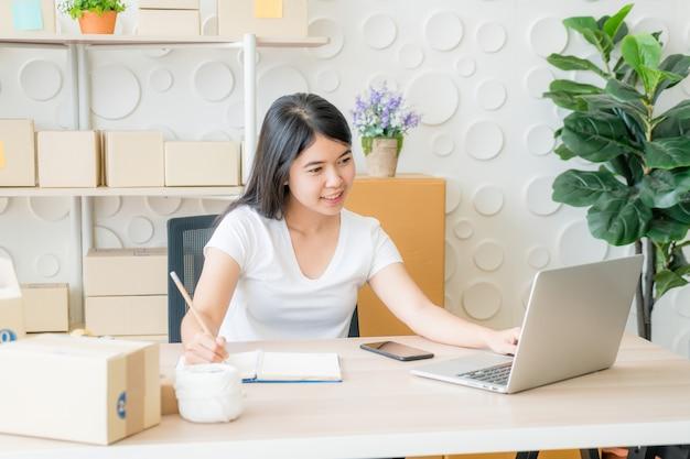 Joven mujer asiática en marcha propietario de una pequeña empresa que trabaja con tableta digital en el lugar de trabajo.