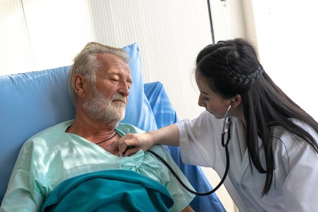 Joven mujer asiática médico uso estetoscopio escuchando órgano interno del anciano paciente en la cama