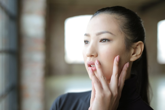 Joven mujer asiática mirando por la ventana durante el día