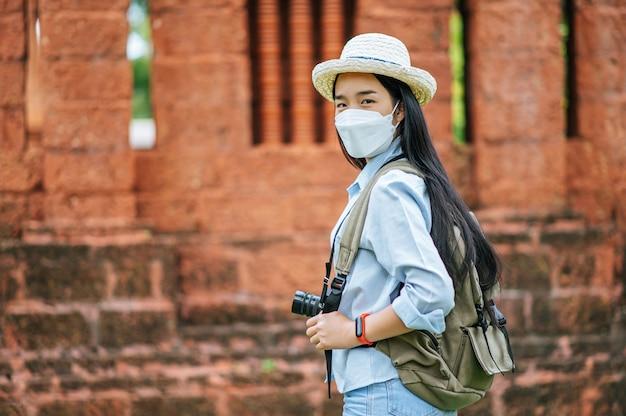 Joven mujer asiática mochilero con sombrero y máscara de protección mientras viaja en un sitio histórico