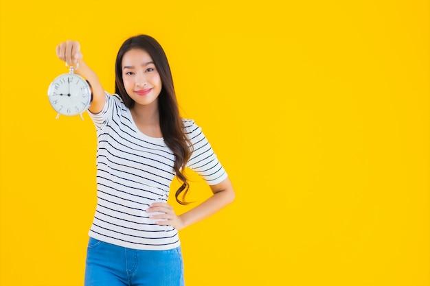 Joven mujer asiática mostrar reloj o alarma