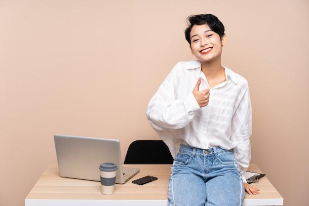 Joven mujer asiática de negocios en su lugar de trabajo dando un gesto de pulgares arriba