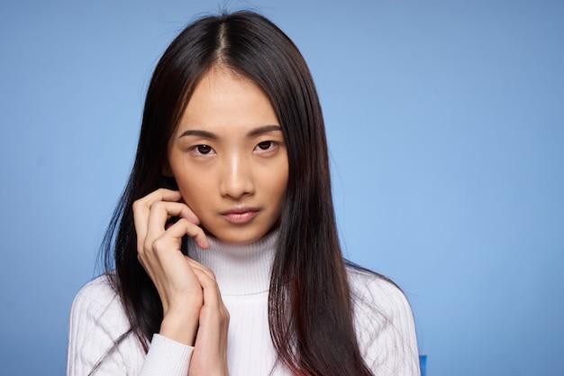 Joven mujer asiática en una pared azul posando, diferentes emociones