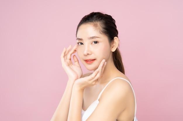 Joven mujer asiática con piel blanca limpia y fresca tocando su propia cara suavemente en pose de belleza