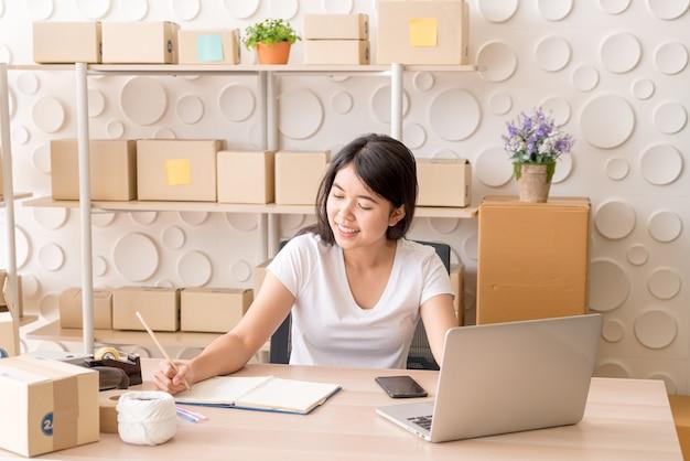 Joven mujer asiática puesta en marcha propietario de una pequeña empresa que trabaja con tableta digital en el lugar de trabajo: venta en línea, comercio electrónico, concepto de envío