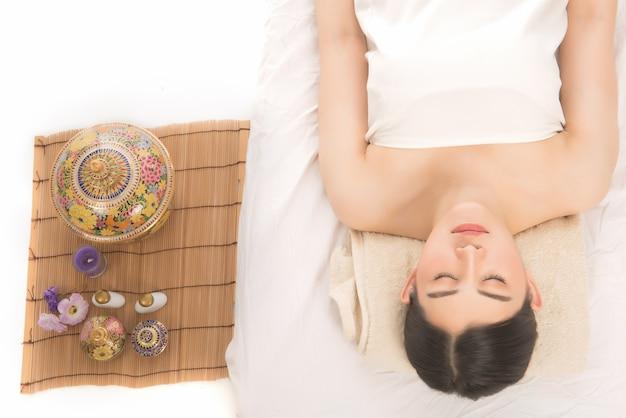 Joven mujer asiática en el salón de spa. tratamientos de aromaterapia orientales tradicionales.