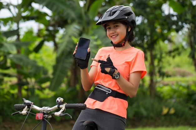 Joven mujer asiática sentada en su bicicleta demostrando teléfono celular móvil