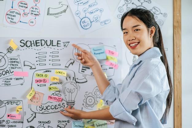 Joven mujer asiática sonriente y actual cepillado del proyecto a bordo en la sala de reuniones, espacio de copia