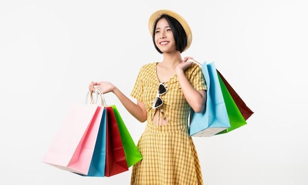 Joven mujer asiática sonriente sosteniendo bolsas de compras multicolores y mirando sobre fondo blanco.