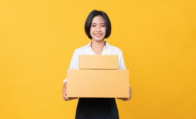 Joven mujer asiática sonriente sosteniendo cajas sobre fondo naranja claro