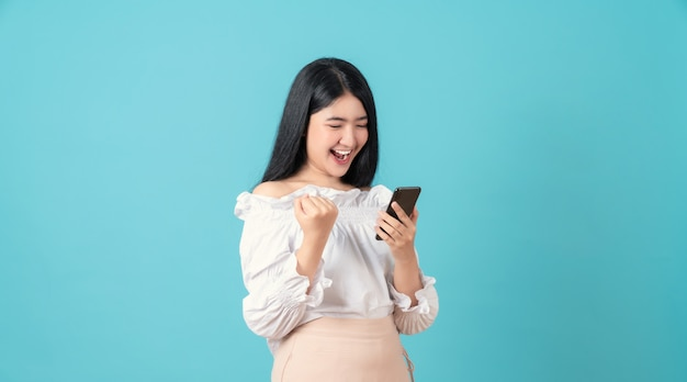 Joven mujer asiática sonriente sosteniendo teléfono inteligente con mano puño y emocionado por el éxito