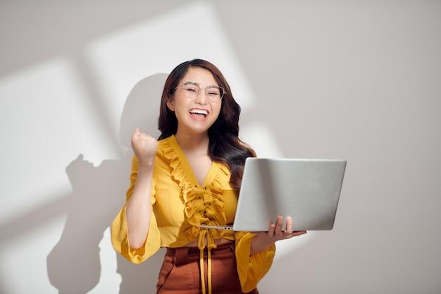 Joven, mujer asiática, sonriente, tenencia, computadora de computadora portátil