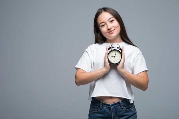 Joven mujer asiática sonrisa con un reloj aislado sobre fondo gris