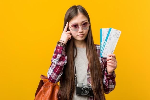 Joven mujer asiática sosteniendo un billete de avión apuntando su sien con el dedo, pensando, centrado en una tarea.