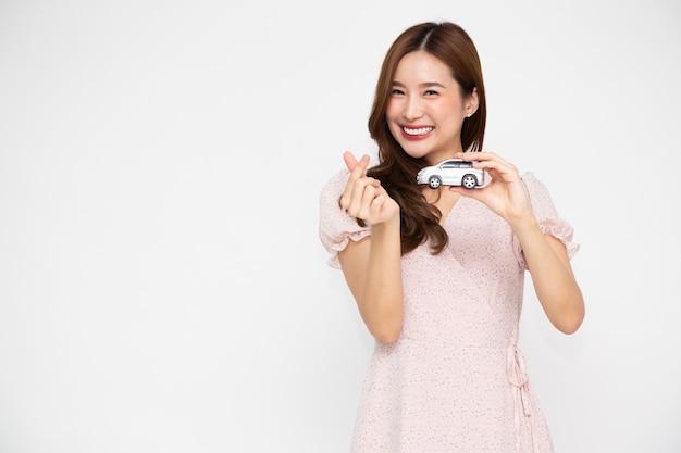 Joven mujer asiática sosteniendo el modelo de coche y mostrando mini signo de corazón aislado sobre fondo blanco.