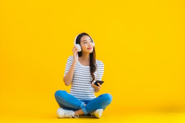 Joven mujer asiática utiliza teléfono móvil inteligente con auriculares