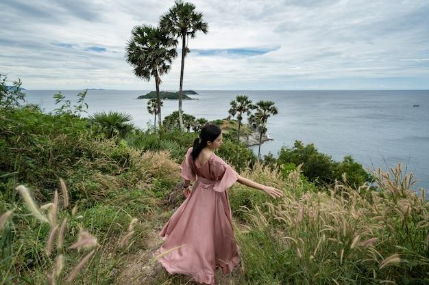 Joven mujer asiática en vestido rosa disfrutar y relajarse en el mirador promthep cape landmark en phuket