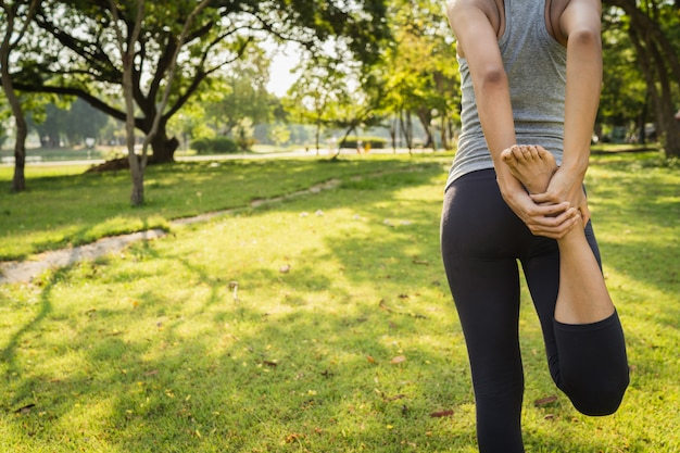 Joven mujer asiática de yoga al aire libre mantiene la calma y medita mientras practica yoga