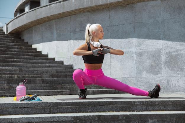 Una joven mujer atlética en camisa y auriculares blancos trabajando escuchando música en la calle al aire libre. haciendo ejercicios de estiramiento. concepto de estilo de vida saludable, deporte, actividad, pérdida de peso.