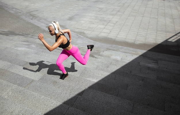 Una joven mujer atlética en camisa y auriculares blancos trabajando escuchando música en la calle al aire libre.
