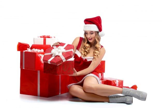 Joven mujer atractiva abriendo regalos de navidad