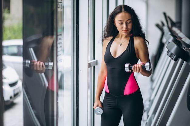 Joven mujer atractiva en el gimnasio con pesas