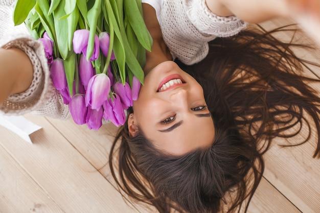 Joven mujer atractiva haciendo selfie con flores en el interior