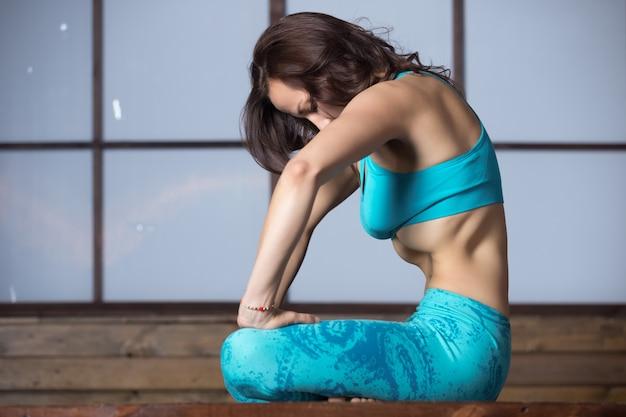 Joven mujer atractiva haciendo upward abdominal lock, estudio incluso