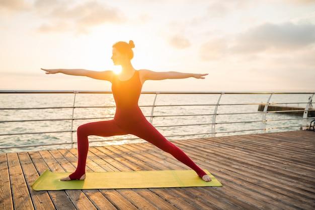 Joven mujer atractiva hermosa delgada haciendo yoga por la mañana al amanecer por el mar, estilo de vida saludable