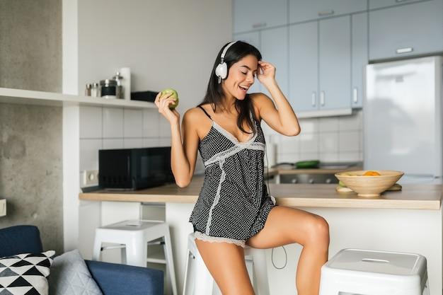 Joven mujer atractiva morena cocinando en la cocina por la mañana, comiendo manzana verde, sonriendo, estado de ánimo feliz, ama de casa positiva, estilo de vida saludable, escuchando música en auriculares, mordiendo