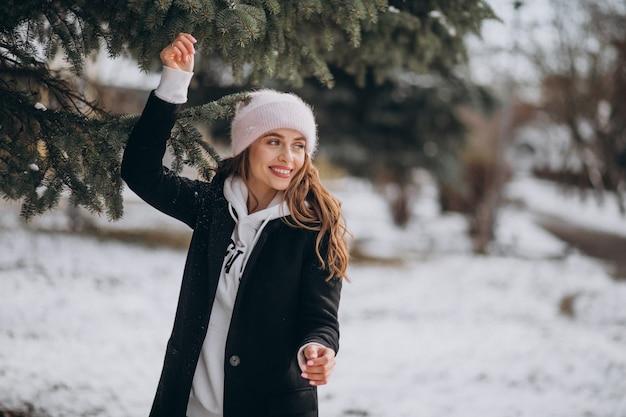 Joven mujer atractiva en un parque de invierno en un lindo sombrero