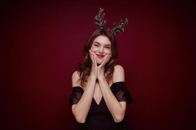 Joven mujer atractiva de pelo castaño vistiendo maquillaje de noche durante la fiesta de navidad, sosteniendo sus mejillas con las palmas levantadas y divirtiéndose