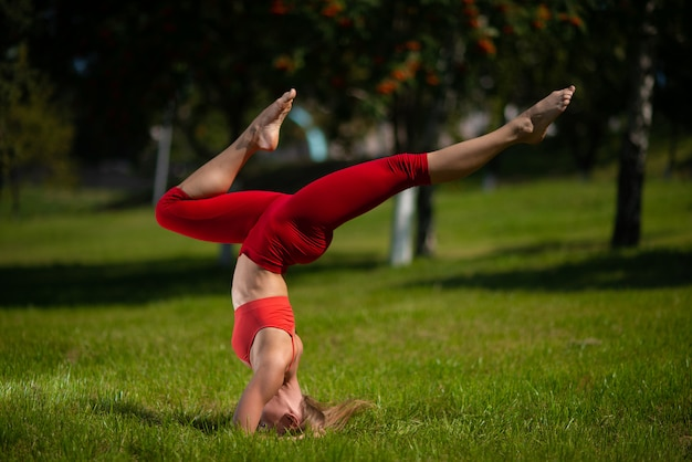 Joven mujer atractiva practicando yoga al aire libre, la niña realiza una parada de manos boca abajo