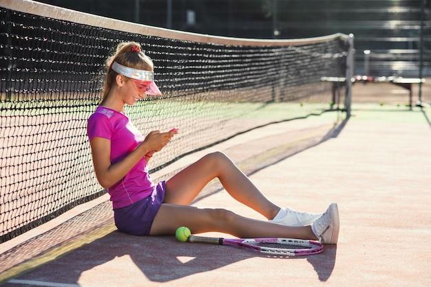 Joven mujer atractiva en uniforme deportivo utiliza teléfono inteligente mientras se relaja en una cancha de tenis. hermosa chica en ropa deportiva tiene un descanso después de un duro entrenamiento en la cancha de tenis al aire libre. concepto de deporte.